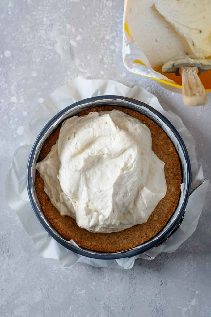 Step-Foto 2 - rohe Cheesecakemasse wird in die runde Kuchenform auf den gebackenen Cheesecake-Boden gefüllt.