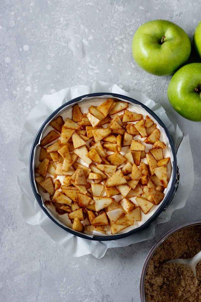 Step-Foto 3: Granny-Smith Äpfel werden im dritten Schritt gemischt mit Zucker und Zimt auf der Cheesecakemasse verteilt