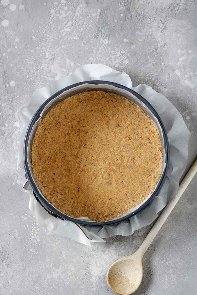 Step-Foto 1 - zeigt den Cheesecakeboden in der 20mm Tortenform ausgekleidet mit Backpapier
