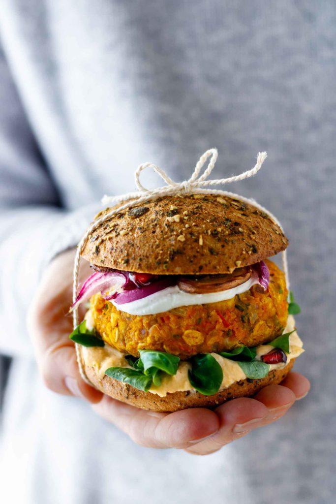 Veggie Burger mit knusprigen Kürbis-Patty auf der Hand serviert