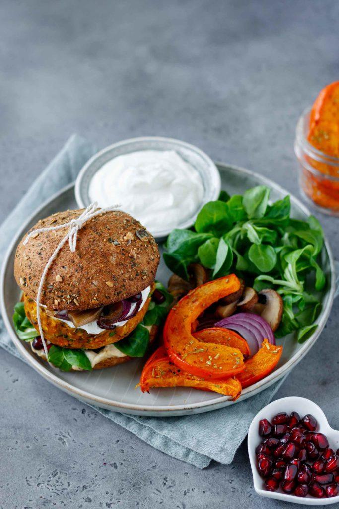 Kürbis Burger serviert auf einem Teller mit gebackenen Kürbisscheiben, Feldsalad, Joghurtdip und Granatapfelkernen