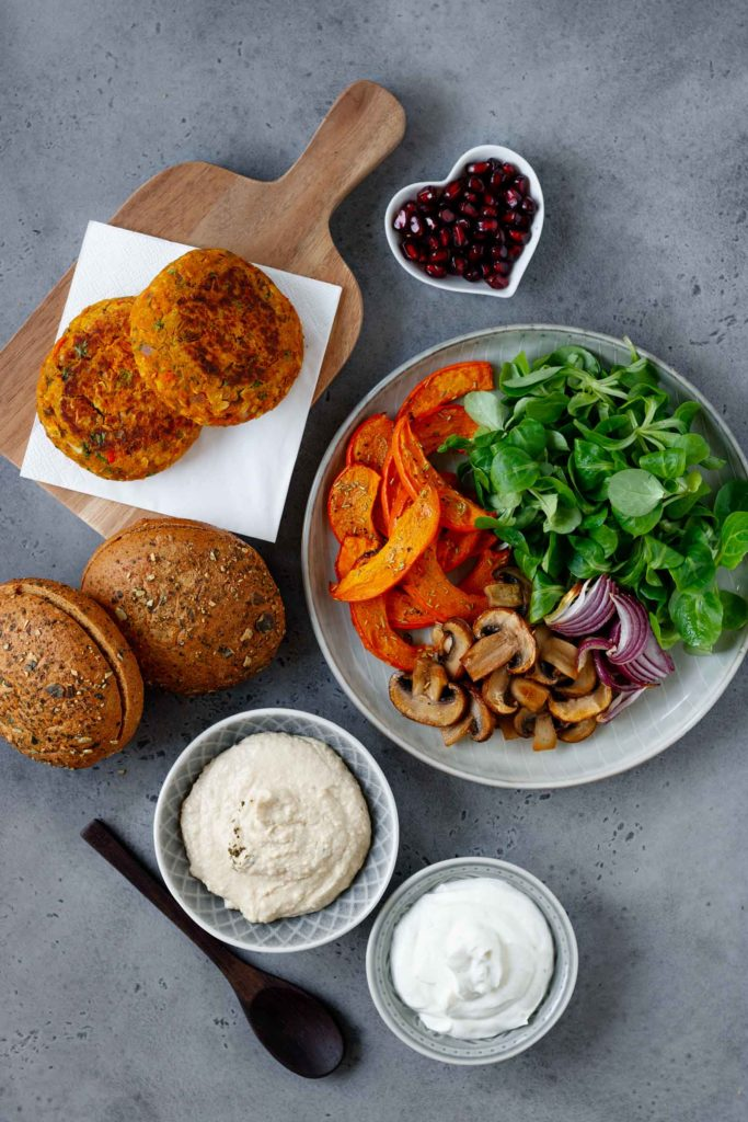 Zutaten des herbstlichen Veggie-Burgers: Kürbis-Pattys, Hummus, Feldsalad, Joghurt-Dip, Granatapfelkerne, gebratene Zwiebel und Champions, gebackene Kürbispommes und die Kürbis-Buns