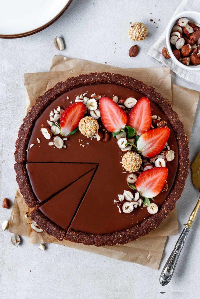 Vegane Valentinstags-Tart mit cremiger Himbeer- und Schokoladenschicht auf knusprigem Nussboden
