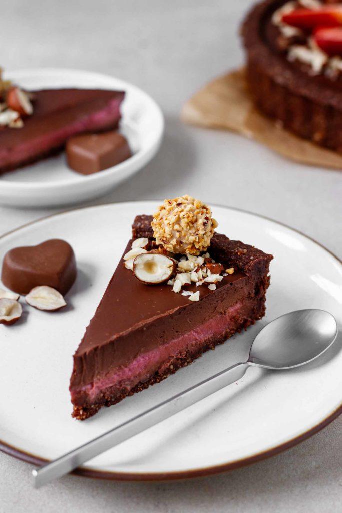 Nahaufnahme des Tartstücks mit cremiger Himbeer- und Schokoladenschicht auf knusprigem Nussboden