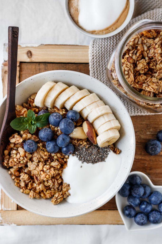 Knuspriges Bananenbrot Granola Rezept, Frühstück im Bett, serviert mit Jogurt, Beeren und Nüssen