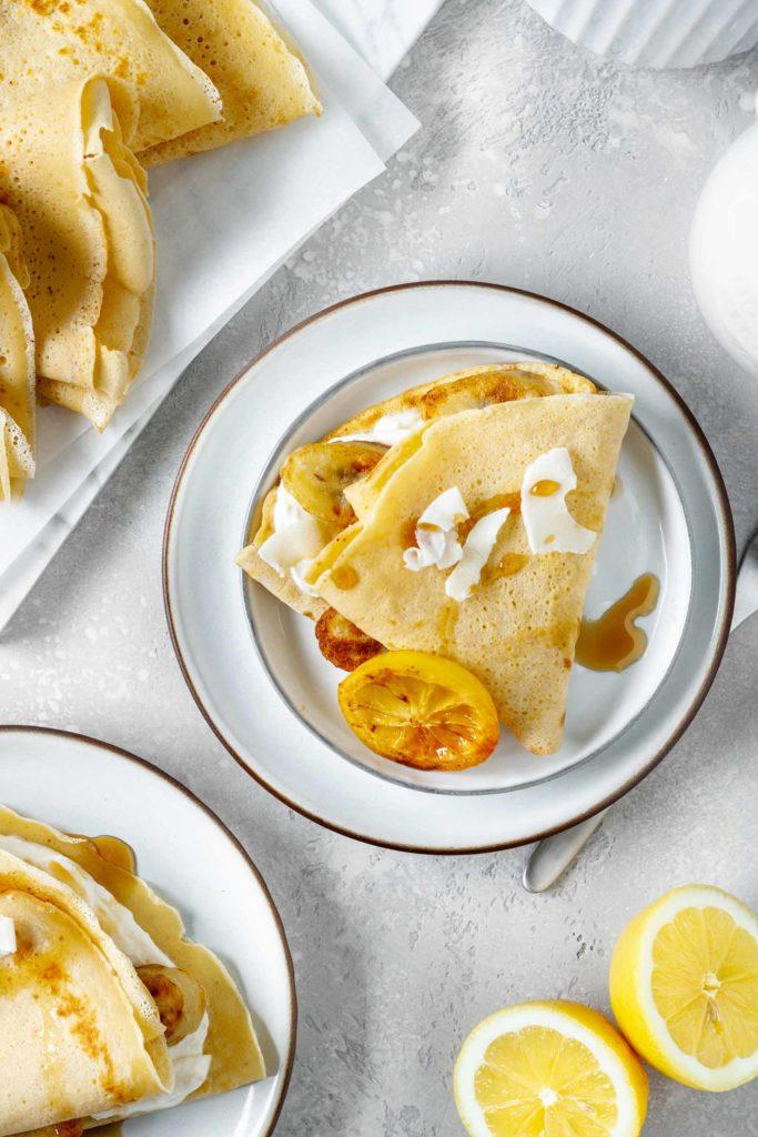 Pfannkuchen gefüllt mit Zitrone-Topfen Füllung, serviert mit karamellisierten Zitronenscheiben, gebratenen Bananen, Kokosflocken und Ahornsirup, Vickys Healthy Dreams