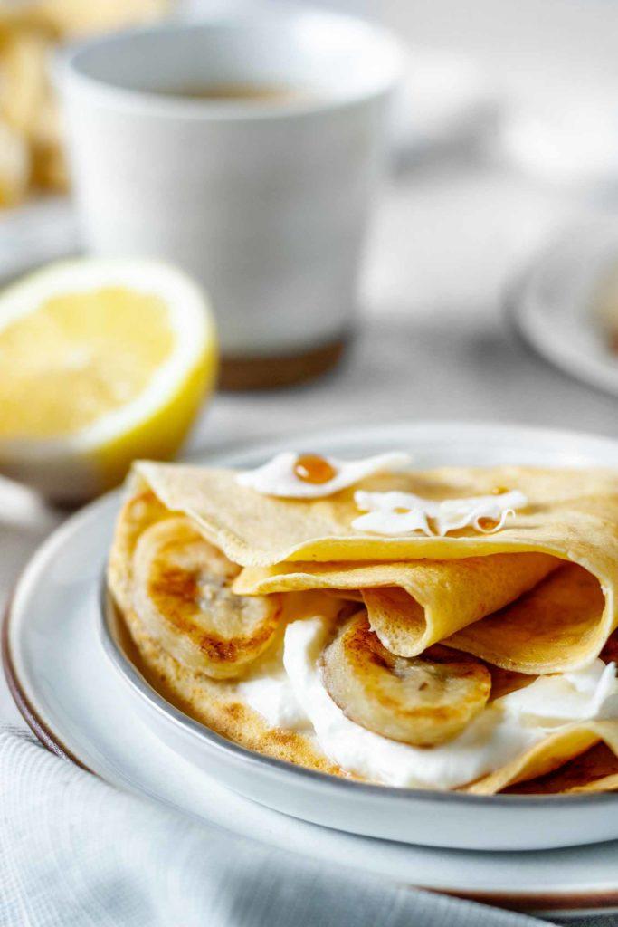 Hauchdünne Palatschinken, traditionell österreichisch, gefüllt mit Zitrone und Topfen, serviert mit Ahornsirup und gebratenen Bananenscheiben, Vickys Healthy Dreams