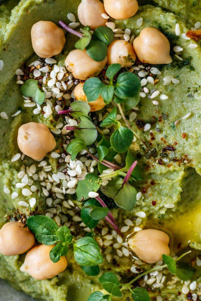 Nahaufnahme des besonders köstlichen Avocado Hummus garniert mit frischen Oregano, Sesam, Kichererbsen und Chili, Vickys Healthy Dreams