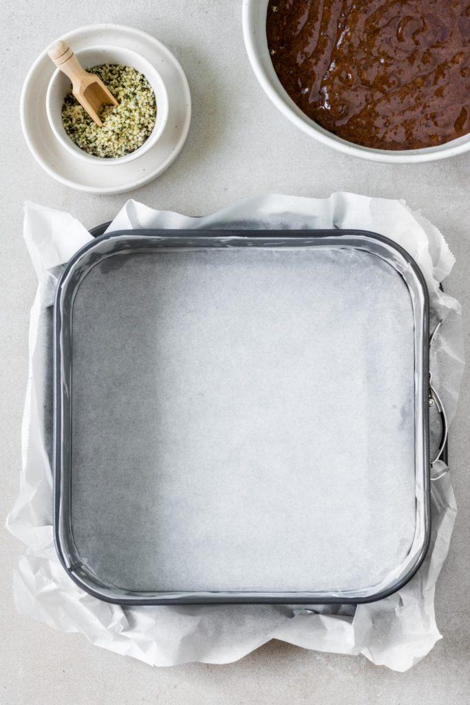 Erster Zubereitungsschritt des Brownie-Rezepts: Eine 24x24cm Backform vollständig mit Backpapier auskleiden