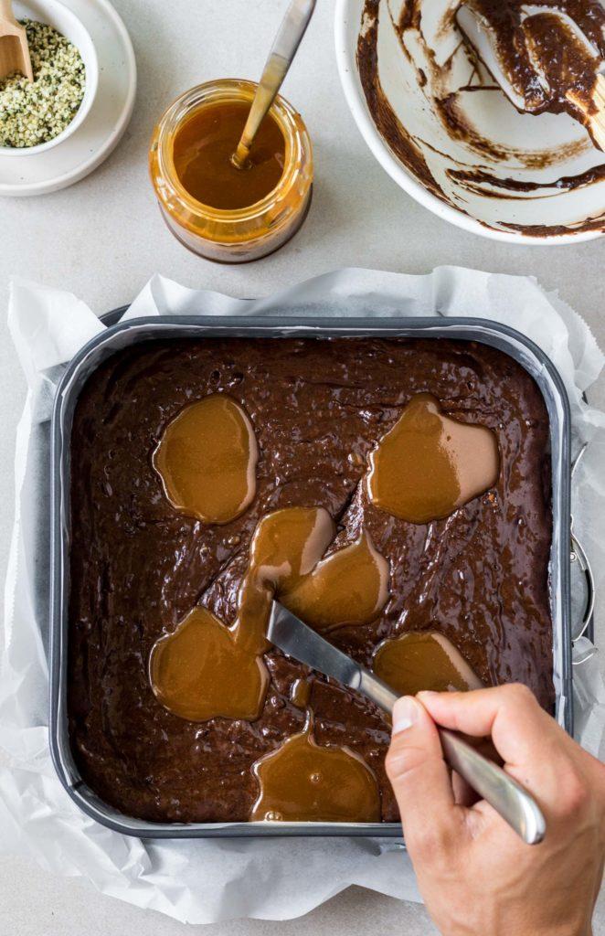Dritter Zubereitungsschritt der Schokoladen-Brownies. Karamell wird mit einem Messer in den Teig eingerührt, Vickys Healthy Dreams