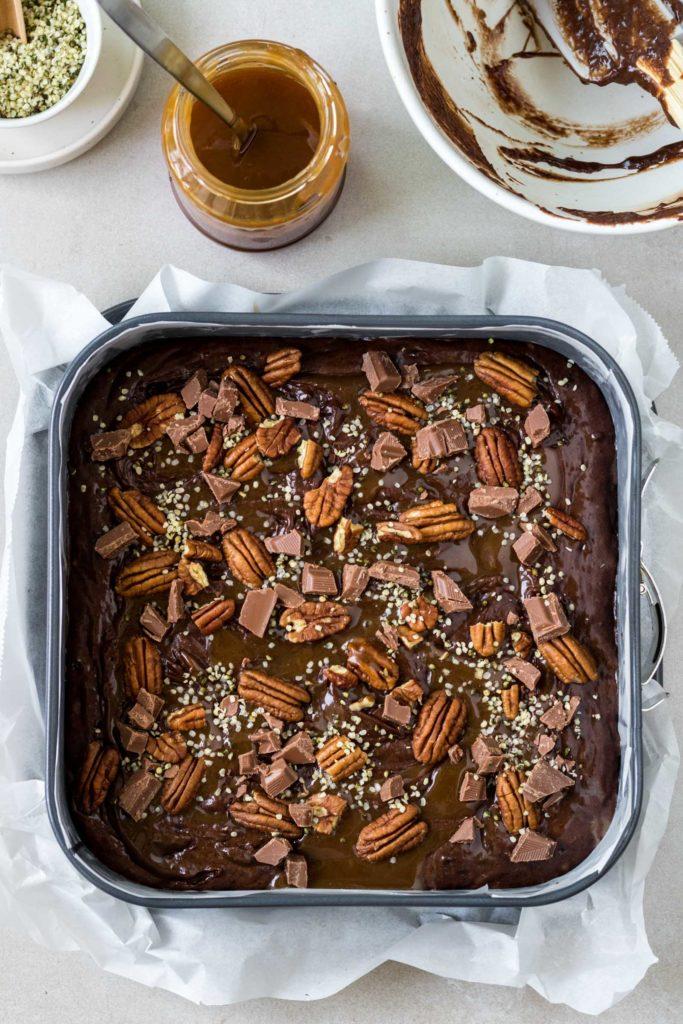 Vierter Zubereitungsschritt des Rezepts: Der Brownie-Teig in der quadratischen Backform wird mit Nüssen, Hanfsamen und Schokolade belegt