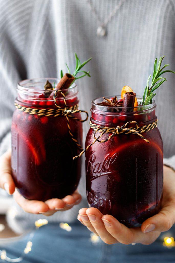 Gesunder Orangen Beerenpunsch, serviert in Gläsern, geschmückt mit Zimtstange, Rosmarinzweigen und Orangenscheiben, Vickys Healthy Dreams